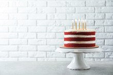Delicious Homemade Red Velvet Cake With Candles On Table Against Brick Wall. Space For Text