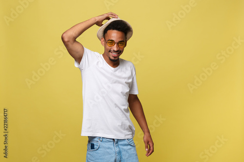Foto  Close up portrait of young afro american shocked tourist , holding his eyewear, wearing tourist outfit, hat, with wide open eyes