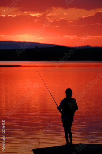 Foto op Canvas Vissen Young Child Kid Person Fishing in Lake or River Sunset