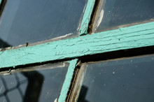 Old Window With Unwashed Windowpane And Chapped Window Frame Painted Green