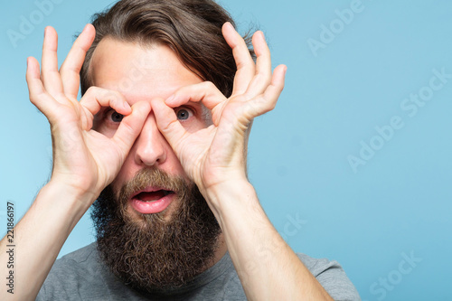 Fototapeta funny ludicrous joyful comic playful man pretending to look through binoculars made of hands