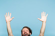 Leinwanddruck Bild happiness enjoyment and laugh. excited man with hands in the air. portrait of a young bearded guy on blue background. emotion facial expression. feelings and people reaction.
