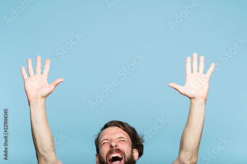happiness enjoyment and laugh. excited man with hands in the air. portrait of a young bearded guy on blue background. emotion facial expression. feelings and people reaction.