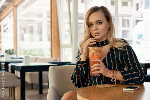 Fotografia  Young woman having good time while sitting in a modern cafe