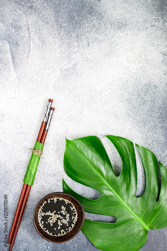 Asian food concept.  soy sauce with white sesame and Chopstick on a gray concrete surface with tropical leaves