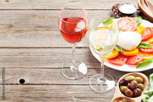 White and rose wine glasses with caprese salad