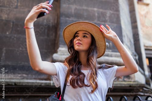 Foto  Young tourist woman taking selfie using smartphone