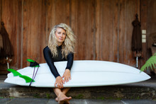Girl In Black Wetsuit With Surfboard Sit On Veranda Steps Of Beach Villa. Surfer Woman Look At Sea Surf And Breaking Waves. Active People In Sport Adventure Camp, Activity On Summer Family Vacation.