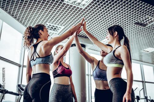 Sporty fit women wearing sportswear giving five each other after having a great fitness class