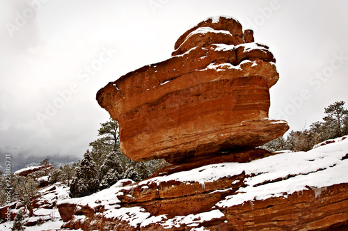 A Red Boulder Is Balanced On A Mountain In A Snowy Winter