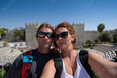 Fotografia  Young couple shot a selfie picture in front of a wall gate in Jerusalem