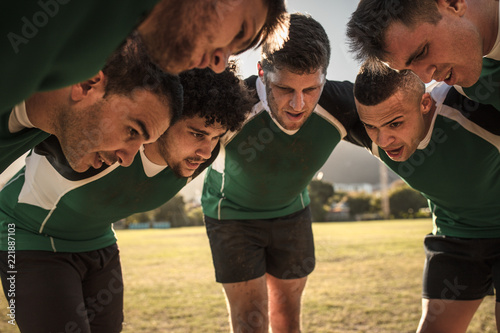 Rugby team in huddle discussing tactics