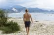 Shirtless man walking on beach, Banda Aceh, Sumatra, Indonesia
