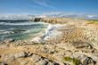 paysage de Bretagne avec une plage de galet et une grosse vague bleue qui arrive pleine d'écume