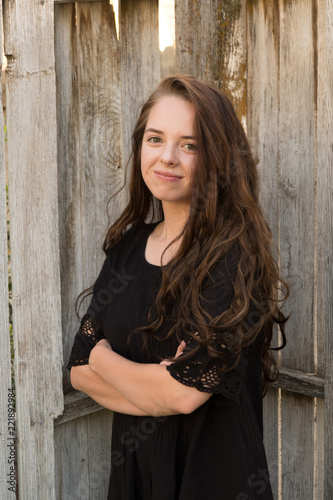 Photo  Brunette woman posing in front of a rustic old wooden fence wearing a black dress standing with arms crossed