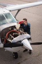 Engineer Filling Oil In Aircra...