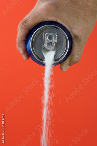 Fotografia  Hand holding soda can pouring lots of sugar in metaphor of sugar content of a refresh drink in unhealthy nutrition, diet, sweet and carbonated drinks addiction and unhealthy food concept