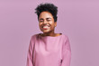 Portrait of overjoyed happiness African American female, widely smiled and close eyes, celebrates her success, poses against lavender background. People, happiness, success concept
