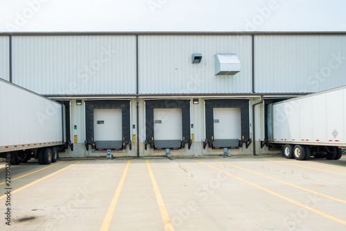 Slika na platnu Warehouse building with 53 foot dry van trailers backed into docking doors