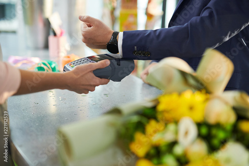 Fotografía  Closeup of modern gentleman paying via smartwatch while buying flowers in flower