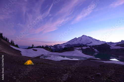 Photo A tent lit up at sunset in the back country with Mount Baker and a colorful sky