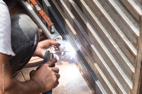 Fotografía Closeup of worker welding auto gate arm onto metal gate
