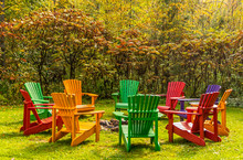 Wooden Adirondack Chairs Arranged In A Circle Around A Fire Pit In The Autumn Colors.