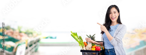 Fototapeta Woman with shopping basket full of groceries in supermarket banner background obraz