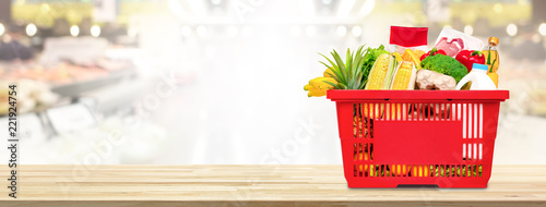 Shopping basket full of food and groceries on the table in supermarket