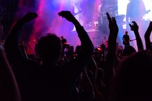Crowd At A Concert Under Purple Lights Of Stage. Radial Blur Effect Creates A Strong Sense Of Emotion And Involvement In The Scene