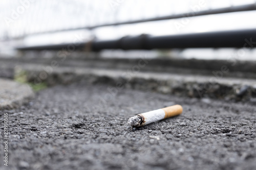 Tossed cigarette which goes out itself left on the asphalt. Fototapet