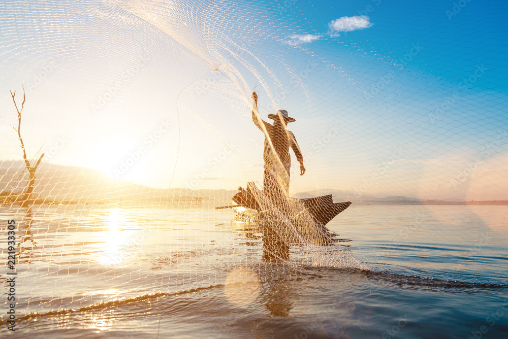 Fototapety, obrazy: Photo shot of water spatter from fisherman while throwing fishing net on the lake. Silhouette of fisherman with fishing net in morning sunshine.