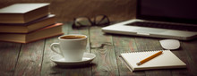 A Cup Of Coffee In The Workplace On A Wooden Table.