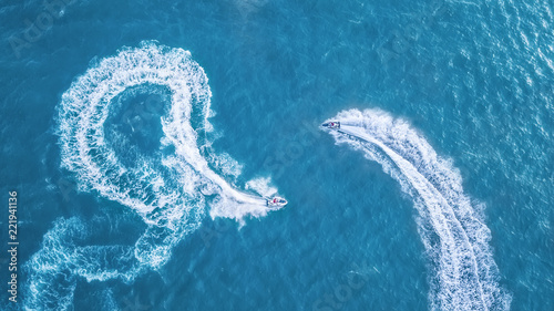 Scooters at the sea surface. Aerial view of luxury floating boat on transparent turquoise water at sunny day. Summer seascape from air. Top view from drone. Seascape with motorboat in bay.