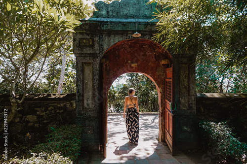 Photo  Woman walks through ornate gateway on a sunny day in Asia