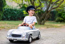 Happy Kid Boy Playing With Big Old Toy Car In Summer Garden, Outdoors. Healthy Child Driving Old Vintage Car Taxi. Laughing And Smiling Kid. Family, Childhood, Lifestyle Concept
