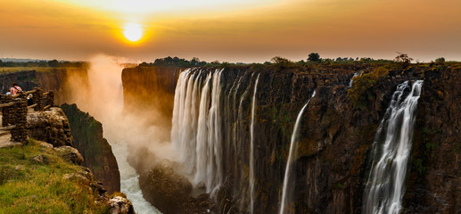 Victoria falls sunset panorama with orange sun and tourists