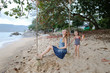 Young happy woman riding swing with little daughter on beach, sea and sand in background. Concept of summer vacations and leisure time.