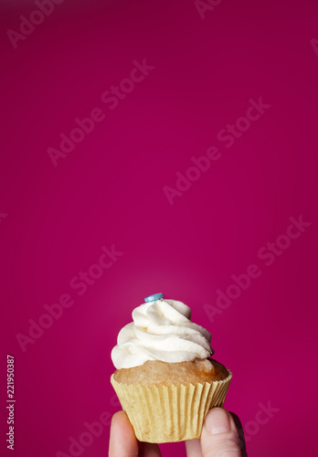 Cupcake with hand on pink background Wallpaper Mural