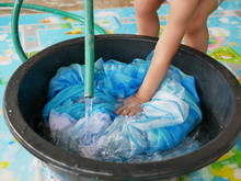 Selective Focus Of A Baby Little Hand Pressing A Dress Down Into The Bucket Filled With Water To Wash It - Child Development Through Doing Housework