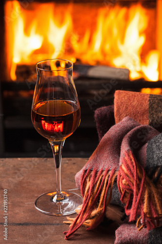 Tuinposter Alcohol a glass of cognac in front of fireplace