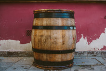 An Oak Barrel With Wine, Against The Background Of The Old Wrapped Wall