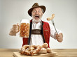 canvas print picture - Germany, Bavaria, Upper Bavaria. The senior happy smiling man with beer dressed in traditional Austrian or Bavarian costume holding mug of beer at pub or studio. The celebration, oktoberfest, festival