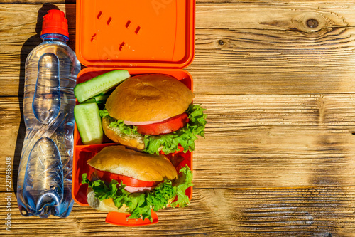 Hamburgers with lettuce in lunchbox and bottle of water on wooden table. Top view