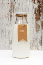 Botella De Leche Con Etiqueta Sobre Fondo Blanco Y Madera Rústica. Vista De Frente