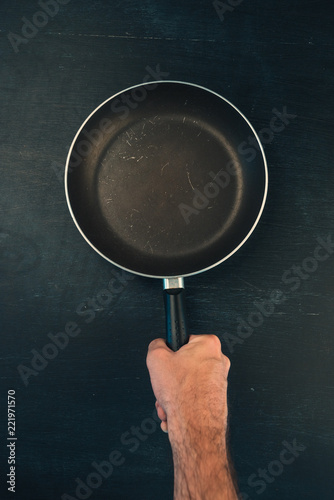 Hand holding frying pan skillet top view