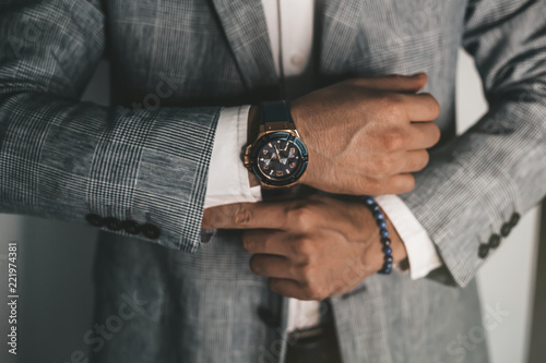 Fototapeta Businessman luxury style. Men style.closeup fashion image of luxury watch on wrist of man.body detail of a business man.Man's hand in a grey shirt with cufflinks in a pants pocket closeup. Toned obraz