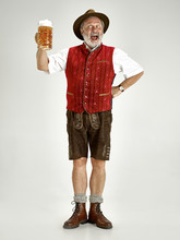 Portrait Of Oktoberfest Senior Man In Hat, Wearing A Traditional Bavarian Clothes Standing With Beer At Full-length At Studio. The Celebration, Oktoberfest, Festival Concept