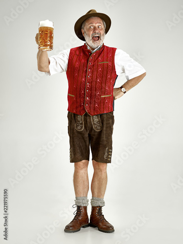 Valokuvatapetti Portrait of Oktoberfest senior man in hat, wearing a traditional Bavarian clothes standing with beer at full-length at studio