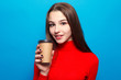 drinks, emotions, people, beauty, fashion and lifestyle concept - emotional happy beautiful woman in red blouse on blue studio background drinking coffee in paper cup smiling, positive, enjoying, morn